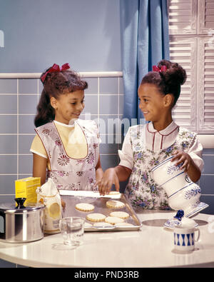 1960s TWO SMILING AFRICAN AMERICAN GIRLS SISTERS IN KITCHEN BAKING COOKIES  - kj5134 PHT001 HARS COPY SPACE HALF-LENGTH INSPIRATION COOKIES SIBLINGS CONFIDENCE SISTERS APRONS SUCCESS HAPPINESS WELLNESS AFRICAN-AMERICANS AFRICAN-AMERICAN EXCITEMENT KNOWLEDGE RECREATION AFRICAN ETHNICITY SIBLING SMILES BAKERS BLACKS COOKS HAIR RIBBONS JOYFUL STYLISH COOPERATION HAIR RIBBON JUVENILES KITCHENS TOGETHERNESS OLD FASHIONED AFRICAN AMERICANS - Stock Image