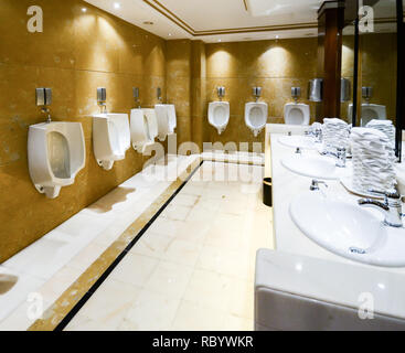 A row of urinals in tiled wall in a public luxurious restroom with sink - Stock Image