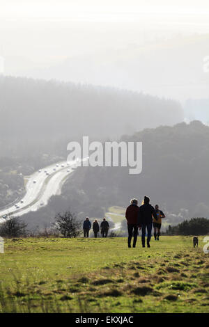 People walking on South Down at Butser hill in silhouette with A3 trunk road - Stock Image