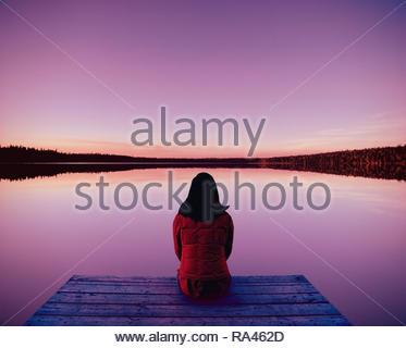 Woman meditating on dock at lake  in evening  in Saskatchewan Canada - Stock Image