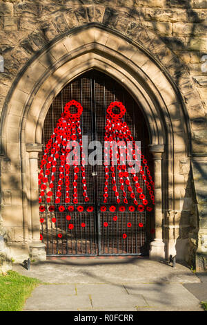 A Gothic Arched church doorway in North Yorkshire decorated with artifical poppies for commemoration of Armistice Sunday November 2018 - Stock Image