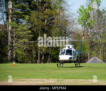 Medivac helicopter coming in for a landing to pick up a patient in Speculator, NY USA for emergency transport to a hospital. - Stock Image