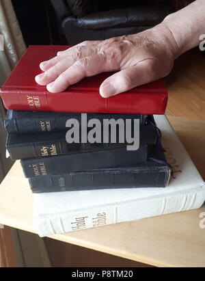 A hand is placed on top of a stack of bibles, ready to swear the truth - Stock Image