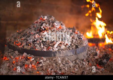 Traditional croatian dish peka in iron bell under glow, food of Croatia - Stock Image