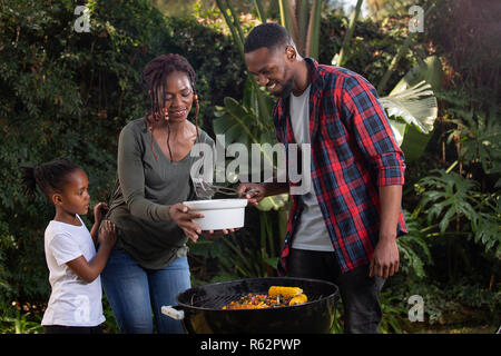 A family barbecuing food outside - Stock Image