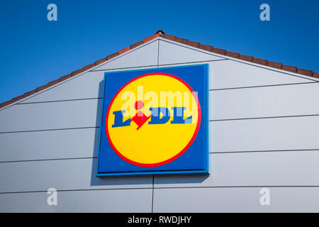 The Lidl sign and logo against a bright blue sky on the front of the Lidl store in Farnham, Surrey. - Stock Image