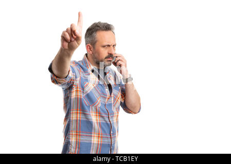 Busy man making wait gesture with index finger while talking on phone isolated on white background - Stock Image