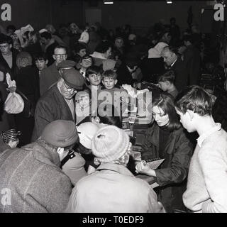 1964, people at  a jumble sell, England, UK. - Stock Image