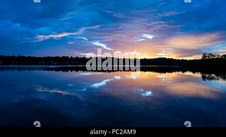 A peaceful blue sky and orange sun glow cloudy sunrise  seascape over sea water with water reflections. Queensland, Australia. - Stock Image