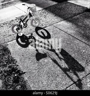 Bicycle on sidewalk with shadow. - Stock Image