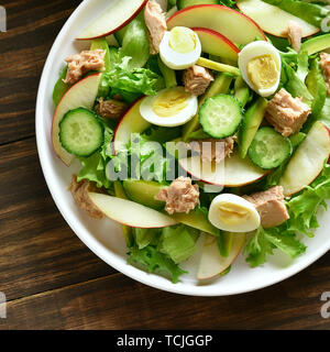Close up of tuna salad with slices of cucumber, avocado, red apple and eggs in bowl on wooden background. Healthy diet food. Top view, flat lay - Stock Image