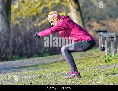 Middle aged woman outside in Winter, stretching and exercising. - Stock Image