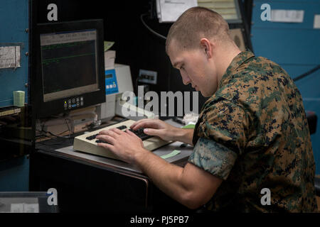 U.S. Marine Corps Sgt. Jordan Catto, air traffic controller, Headquarters & Headquarters Squadron, Marine Corps Air Station (MCAS) Camp Pendleton, gives a pilot clearance to take off while working from the Radar Air Traffic Control Facility at MCAS Camp Pendleton, California, Aug. 24, 2018. Pilots contact the air traffic control prior to departure or arrival to the airfield to avoid collision with other aircraft within the airspace. (U.S. Marine Corps photo by Lance Cpl. Betzabeth Y. Galvan) - Stock Image