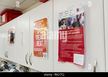 Various posters on the cupboards in a hospital treatment room. - Stock Image