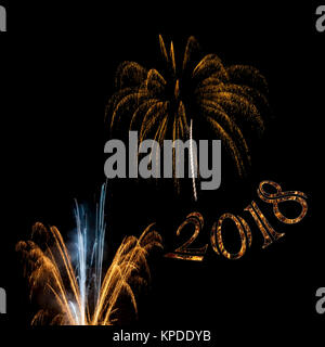 Elegant gold and white exploding fireworks 2018 in black night sky New Years Eve holiday background - Stock Image