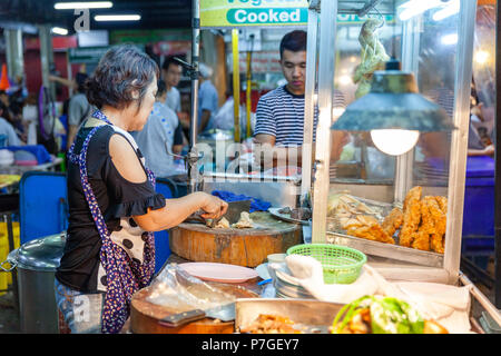CHIANG MAI, THAILAND - AUGUST 27: Food vendor prepares chiken for sale at the Saturday Night Market (Walking Street) for sale on August 27, 2016 in Ch - Stock Image