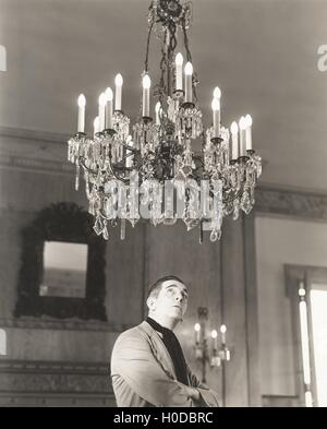 Man staring at chandelier - Stock Image