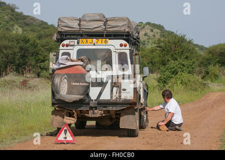 Rough tatty old Land Rover Defender 110  in the Serengeti  National Park Tanzania. Broken down - Stock Image