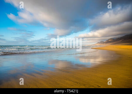 Lonely beach coloured and reflected with beautiful mountain background  with cloudy sky - summer tropical vacation concept in free sandy scenic place  - Stock Image