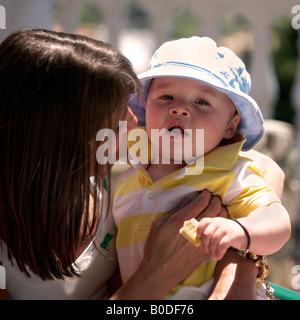 Mother and Toddler sitting at outdoor table wearing blue hat, biscuit crumbs on lips - Stock Image