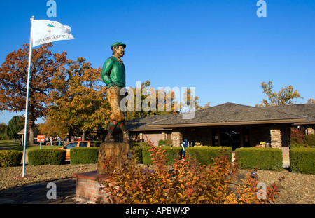 Mulligan, a wooden statue, looks out over the HIghlands Club House at Highlands Golf Course in Bella Vista, Ark. - Stock Image