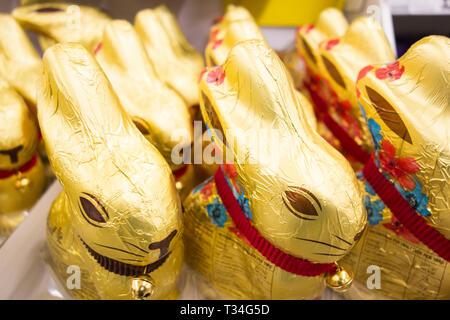 Lindt Golden Milk Chocolate and Dark chocolate bunnies on a supermarket shelf in the UK - Stock Image