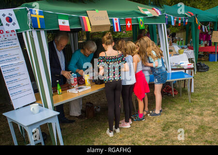 A group of young girls crowd around the Tombola Stall at Ewelme Harvest Fete, Oxfordshire - Stock Image