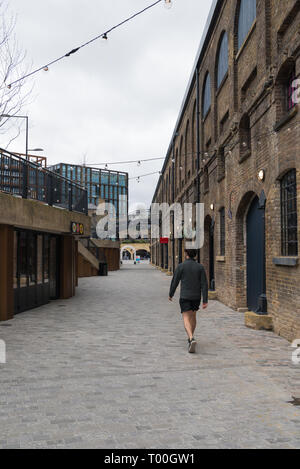 A lone man walks along Stable Street in Coal Drops Yard, a refurbished area of Victorian buildings at Kings Cross, London, England, UK - Stock Image
