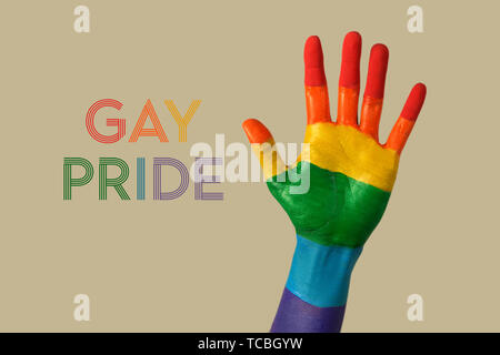 closeup of the palm of the hand of a person, painted as the rainbow flag, and the text gay pride written with the colors of the rainbow flag, against  - Stock Image