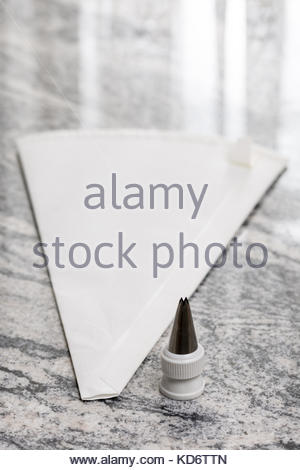 White pastry piping bag on the grey granite background table. - Stock Image