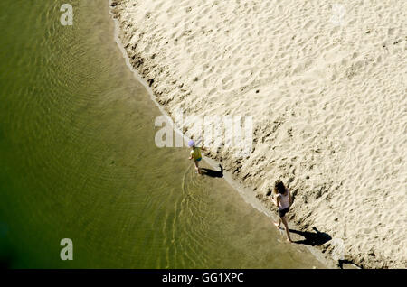 Mother and son walking along the shoreline of a river beach in the Ardeche region of France. Taken from above. - Stock Image