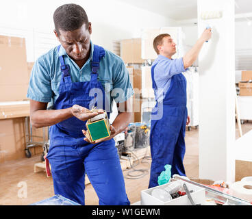 Two efficient glad male builders working at indoors building site - Stock Image