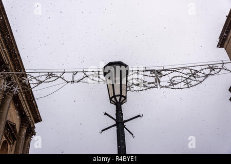 Decorative lamp housing from a street light in front of festive decorations between 2 buildings with a daytime grey white sky with (fake) snow falling - Stock Image