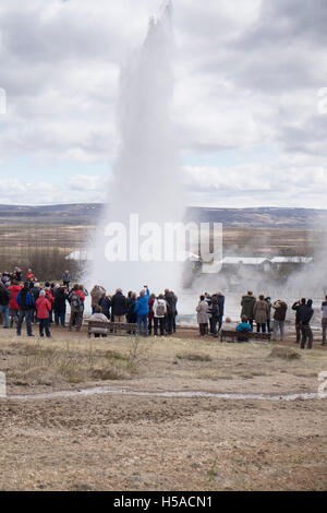 Geysir, South Iceland: Group of tourists looking at geyser eruption - Stock Image