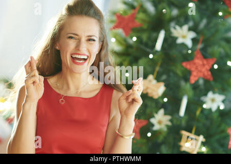smiling modern woman in red dress with crossed fingers near Christmas tree - Stock Image
