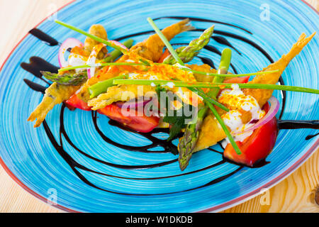 Deep fried sprats served on blue plate with creamy ginger sauce, fresh tomatoes, asparagus, onions and balsamic - Stock Image