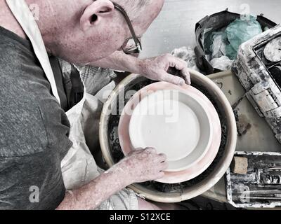 Potter on the wheel make pie plate - Stock Image