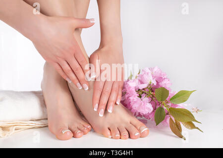 Female legs with bare feet and hands with french manicure and pedicure on white towel in spa salon and decorative pink flower in background - Stock Image