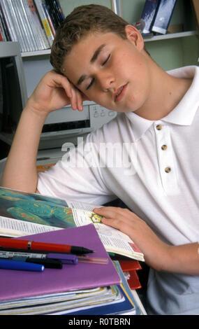 teenage schoolboy falling asleep over his homework - Stock Image