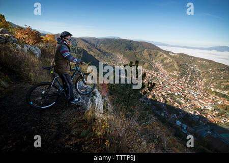 Cyclist looking at city while standing on cliff - Stock Image