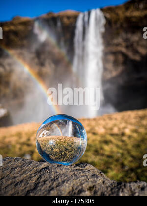 Seljalandsfoss, a majestic and powerful waterfall in Iceland in a sunny spring day with a raibow - Stock Image