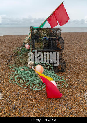 Lobster/crab pots with flag markers, bouys and rope on a shingle beach with sea horizon in background - Stock Image
