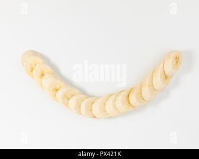 chopped banana on a white background - Stock Image