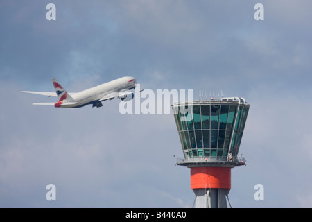 British Airways Boeing 777 taking off in the background of London Heathrow control tower. - Stock Image