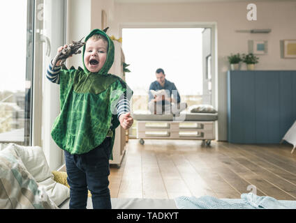 Happy boy in a costume playing with toy figure at home - Stock Image