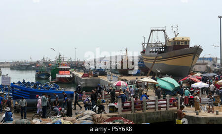 The crowded fishing port of Essaouira in Morocco.  Fish are landed, sold, cooked and eaten all on the quayside - Stock Image