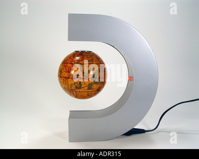 Floating magnet globe as symbol for physical effects and or the instability of the world economy and the like - Stock Image
