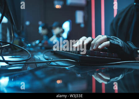 Close-up of unrecognizable computer engineer in fingerless gloves sitting at table and typing on keyboard - Stock Image