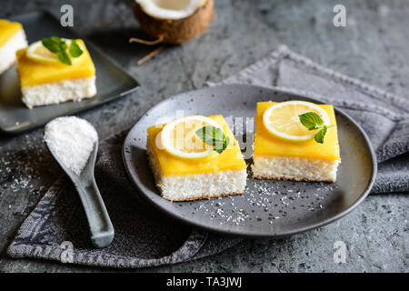 Delicious coconut bars with lemon curd on a plate - Stock Image