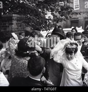 1960s, historical, just married couple get showered in confetti by the bridal car, - Stock Image